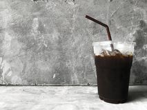 Ice Black Coffee on the cement Background royalty free stock image