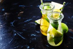 Ice black and green tea with lemon, lime and ice in the jug, selective focus royalty free stock image