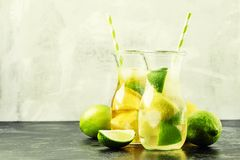 Ice black and green tea with lemon, lime and ice in the jug, selective focus royalty free stock photography