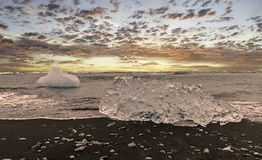 Ice block on a black sandy beach. Ice blocks from the glacier lagoon at Jökulsárlón float into the sea and get pushed onto the beach by waves royalty free stock images