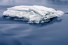 Ice block in blue water Royalty Free Stock Photos