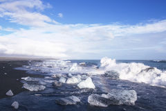 Ice blocks on a black sand beach Stock Images