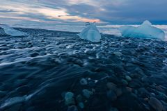 Ice blocks on the black sand beach during sunset in Iceland stock images
