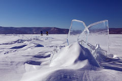 Ice with the blue sky and skiers. Two skiers are running on the ice of Baikal lake with the block of ice on the foreground Royalty Free Stock Photos