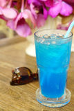 Ice blue soda on timber table Stock Photo