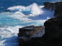 Ice blue tropic wind swell pounds the cliffs, Hawaii. South shore of Oahu's beautiful black lava cliffs, meet the crystal blue channel waters Stock Photo