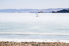 Ice boating competitions in the winter on lake Baikal in clear weather in beautiful mountains area. Stock Photo