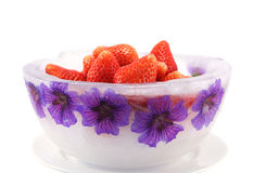 Ice Bowl with Strawberries. Decorative bowl made of ice and perennial geranium flowers, filled with tasy strawberries and isolated on a white background royalty free stock images
