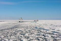 Ice breaker assist general cargo ship in ice navigation. At Bothnia Bay stock image