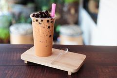 Ice bubble milk tea in takeaway glass. On wooden plate - burry background royalty free stock photography