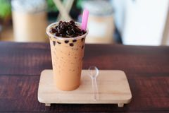 Ice bubble milk tea in takeaway glass. On wooden plate - burry background royalty free stock images