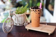 Ice bubble milk tea in takeaway glass. On wooden plate - burry background stock photo