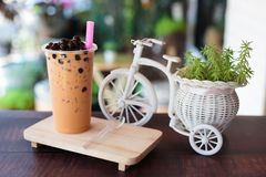 Ice bubble milk tea in takeaway glass. On wooden plate - burry background royalty free stock photo