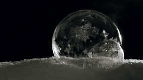 Ice bubbles freezing. Fast Freezing Soap bubbles. Ice ball with flying snowflakes flowers on snow and black background in cold winter. For Christmas and New Year stock video footage