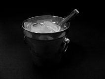 Ice Bucket. An isolated ice bucket filled with ice cubes in a black environment, filled with ice stock photography