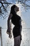 Ice bucket challenge. Woman pours iced water from a bucket Royalty Free Stock Images