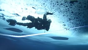 ICE CAMP SARGO, MARCH 2016, Diver dives direct under ice shell. A Navy diver dives under the ice shell in the Arctic Ocean stock video footage
