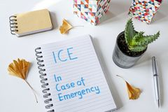 ICE In Case of Emergency written in notebook. On white table Royalty Free Stock Image