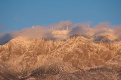 Ice Castles. Communications towers on the summit of Sandia Peak in Albuquerque, NM are covered in ice from a recent storm. The breaking clouds and setting sun stock images