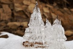 Ice castles against a background of brown rocks. stock photos