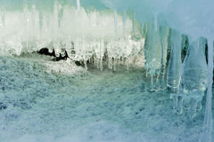 Ice Cave. Ice and icicles forming a cave-like structure beautifully illuminated by sunlight royalty free stock photography