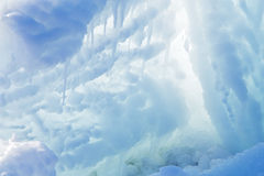 Ice cave. Exit with icicles at sun light royalty free stock image