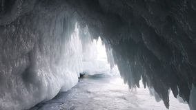 Ice cave grotto in winter. Ice icicles at the entrance to the cave at Olkhon island in Siberia in Russia. Travel in frosty weather stock image