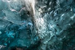 Ice cave beneath glacier in Iceland. Ice cave located beneath glacier among ice mountain in Iceland, it is mesmerizing landmark royalty free stock images