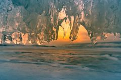 Ice cave with sunset sky background close up. Winter season natural landscape stock image