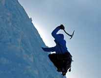 Ice Climber. Climbing a frozen wall in mountains Stock Image