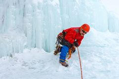 Ice climber arranges rope protection on the glacier royalty free stock image