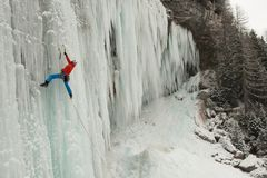 Ice climber on a frozen waterfall royalty free stock images