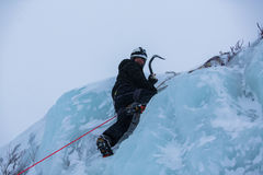 Ice climber scaling ice wall Royalty Free Stock Image