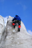 Ice-climbing. Climber accomplishes an ascent on an ice wall Royalty Free Stock Photography