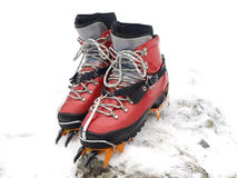 Ice climbing boots and crampons. Ice climbing boots with crampons on edge of snow covered rock royalty free stock image
