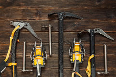 Ice climbing equipment on dark wooden background, top view. Trav. Ice climbing equipment: ice tools, ice ax, ice screws, crampons on dark wooden background, top Stock Photo