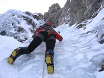 Ice climbing girl. Strong and brave young girl, during ascent in a frozen waterfall Stock Image