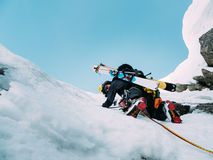 Ice climbing: mountaineer on a mixed route of snow and rock during the winter stock photography