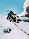 Ice climbing: mountaineer on a mixed route of snow and rock duri Stock Images