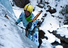 Ice climbing the North Caucasus. Climbing a frozen waterfall with ice tool Royalty Free Stock Image
