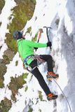 Ice climbing in winter. Man in green jumper climbing an ice wall Royalty Free Stock Photos
