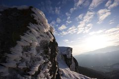 Ice and clouds. Rocks coverd with ice in front of shiny sky and clouds.peak ispolin in stara planina mountain,bulgaria royalty free stock photo