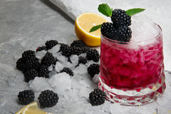 Ice coctail with mint and blackberries,in a pink glass on a grey background, berries, mint and a slice of lemon on a. Refreshing cocktail with fresh green mint Royalty Free Stock Photos