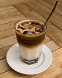 Ice coffee 1. A shot of a glass of ice cold coffee on a wooden table. Front of the glass in focus Royalty Free Stock Photography