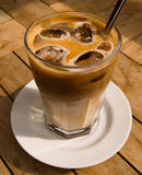 Ice coffee 2. A shot of a glass of ice cold coffee on a wooden table. Back of the glass in focus Stock Image