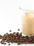 Ice coffee. Glass of ice coffee with ice cube and coffee beans around Royalty Free Stock Photos