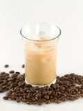 Ice coffee. Glass of ice coffee with ice cube and coffee beans around Stock Image