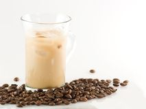 Ice coffee. Glass of ice coffee with ice cube and coffee beans around Stock Photography