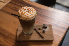 Ice coffee caramel macchiato. On wooden table Royalty Free Stock Photography