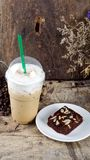 Ice Coffee and chocolate brownie. Ice coffee put on a wood table with dark roasted coffee beans Royalty Free Stock Photos